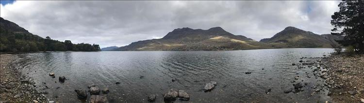 Wide andlge shot of a loch with the angular hills and mountains beyond the stoney beach