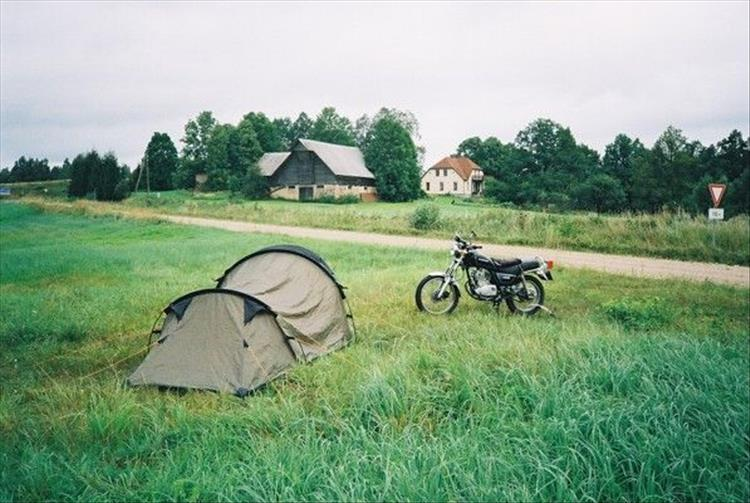 A small tent in a field with Mark's Suzuki GN125 parked next to it