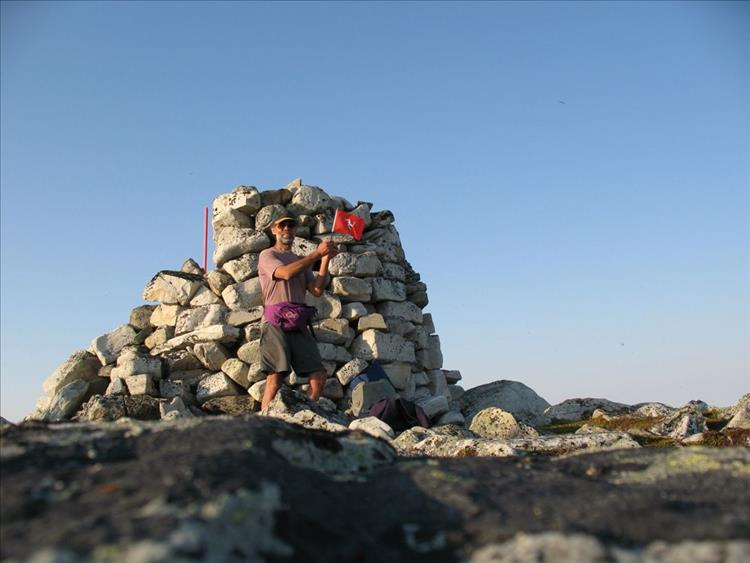 Mark proudly waves a small Isle Of Man flag next to a cairn at Cape Nordkinn