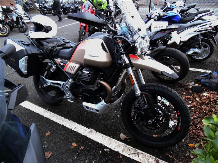 The large v-twin Moto Guzzi adventure bike in the car park ready to ride