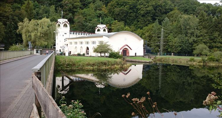 A large white building set among trees and a calm small reservoir. The building is stylish and quite old