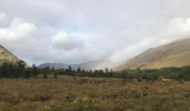 On the rugged moors and mountains of Scotland we can make out a rainbow disappearing into a valley