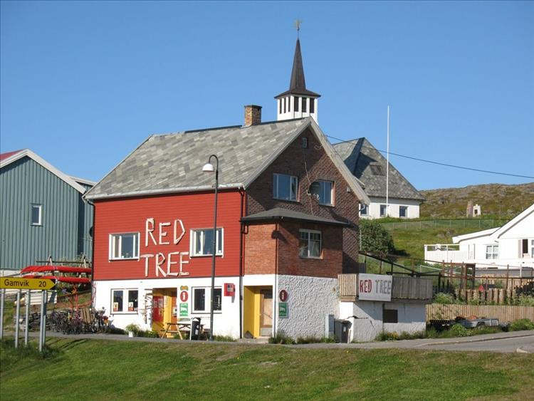 A stout flat red building with a simple Red Tree lettered on the side