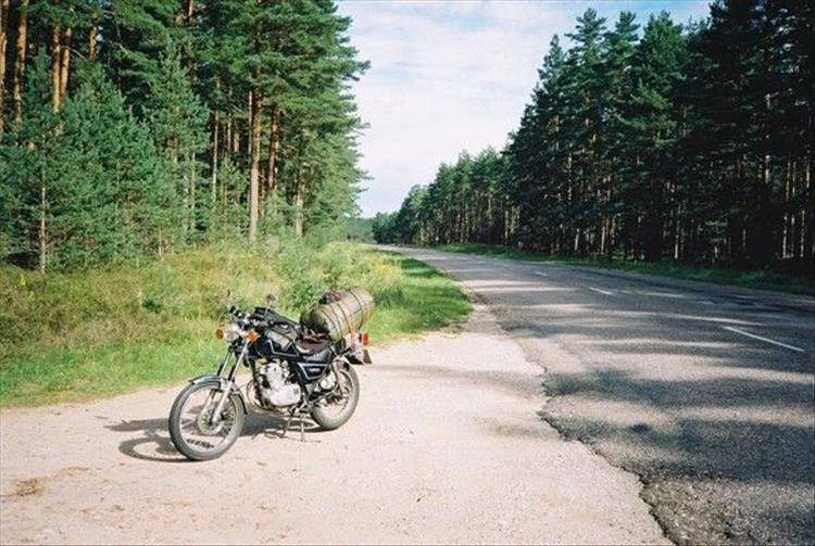 The bike with light luggage at the side of a tarmac road lined with thick green lush trees