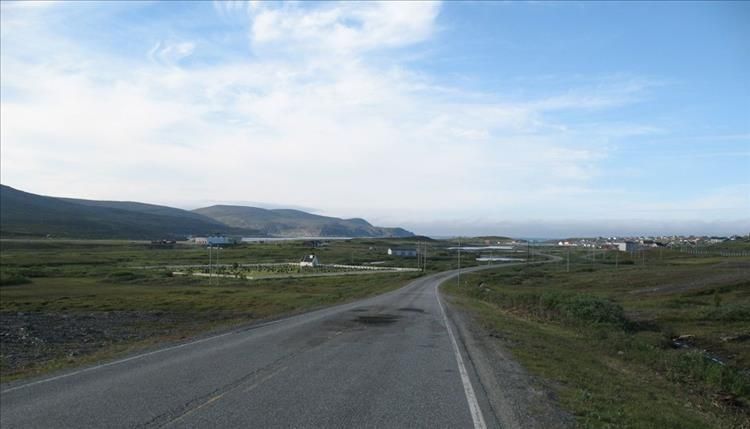 A road winds along a treeless plain to a remote small town in the far north.