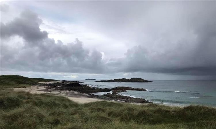 Sands, hardy grasses, rocks and the sea under turgid skies of Iona
