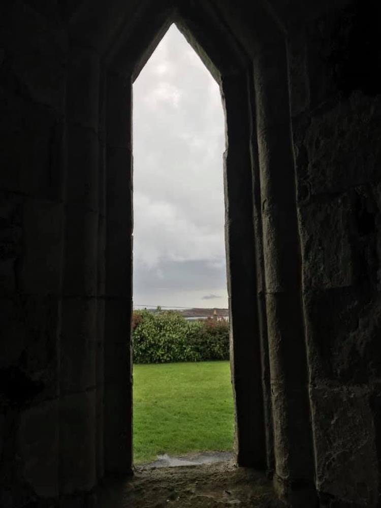 Looking through the tall narrow slit window out to the countryside beyond the abbey