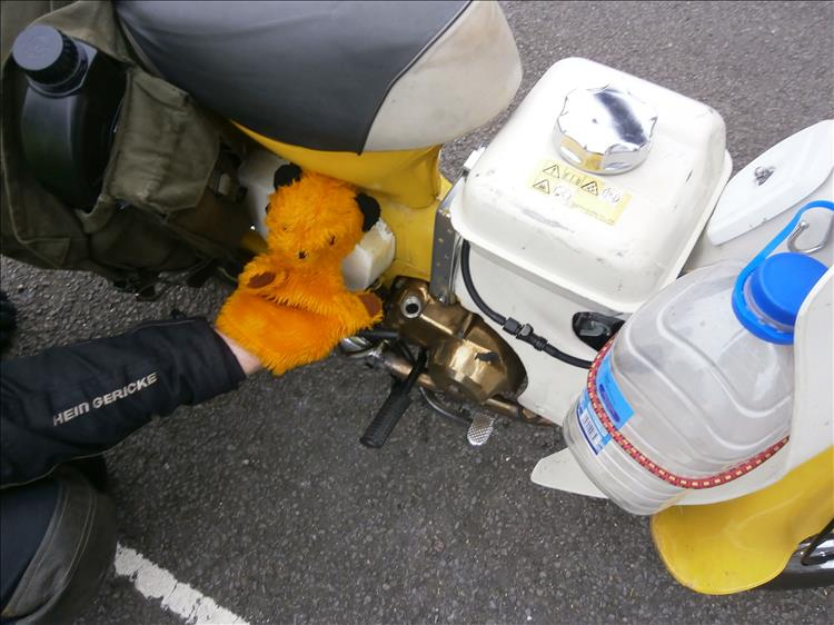 The puppet sooty beside the now golden coloured engine cases of the overheated motorcycle
