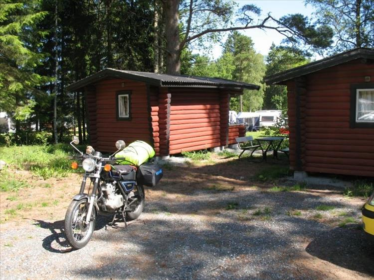Mark's GN125 by 2 small wooden cabins and immensely tall pine trees in Sweden