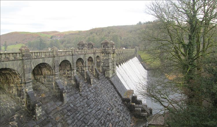 The stone Victorian dam has water splashing through the overspill channels, behind are the Welsh hills