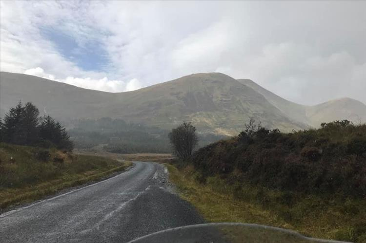 Round fat mountains and hills in changeable weather riding through The Highlands