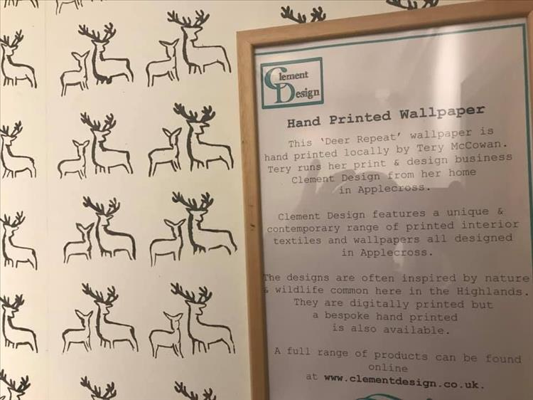 Simple hand printed wallpaper with a plaque describing who makes it and their details