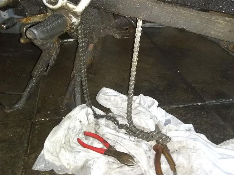 The chain hangs down from the bike's swingarm while being fitted