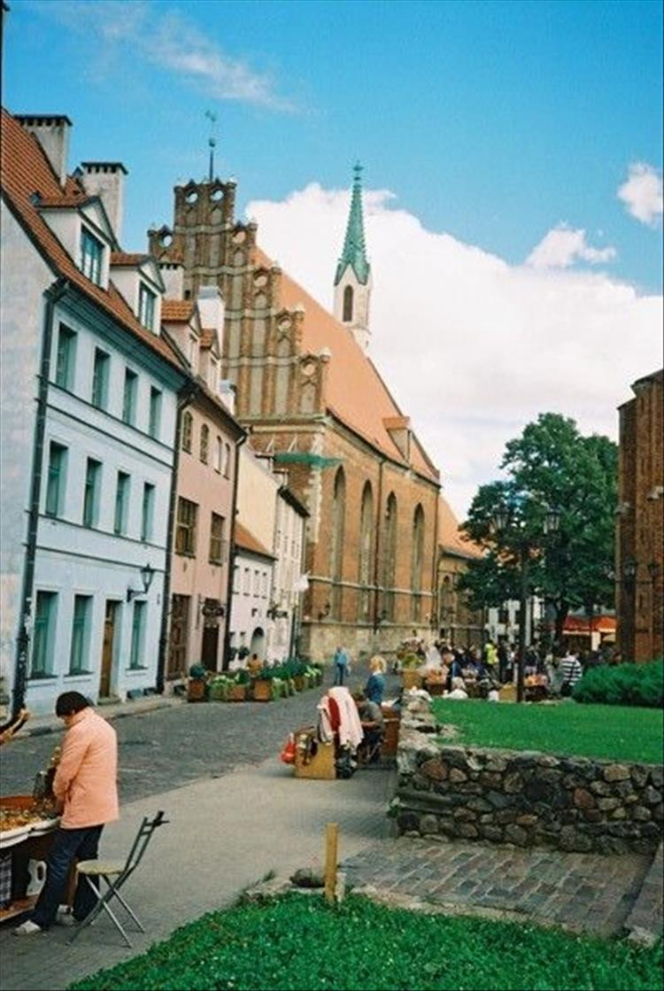 4 storey pastel painted houses and a large brick built church on a quiet street in Riga