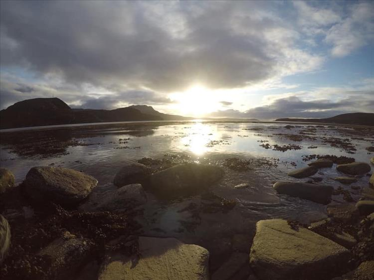 The sun is low in the sky reflecting off the water with rocks and seaweed and mountains