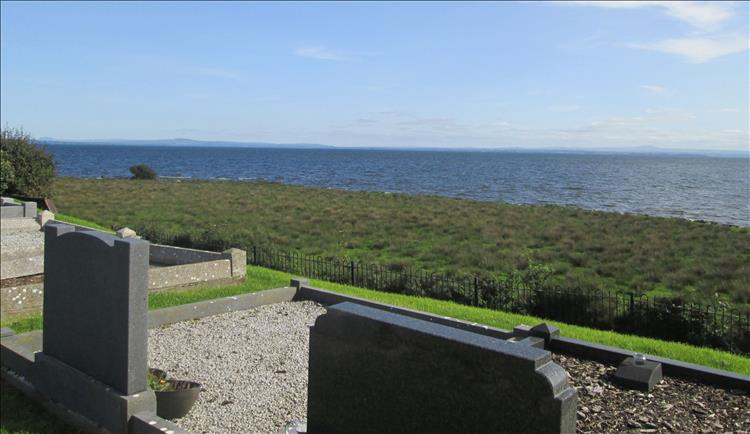 In the close foreground are to modern graves overlooking the vast waters of Lough Neagh