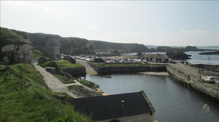 Ballintoy Harbour. Sturdy walls and buildings at the foot of steep cliffs on the Irish coast
