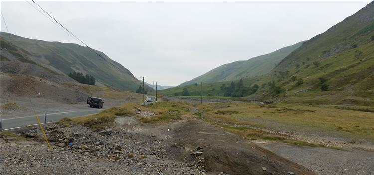 Looking along a Welsh valley with scree covered hillside and the road winding off into the distance