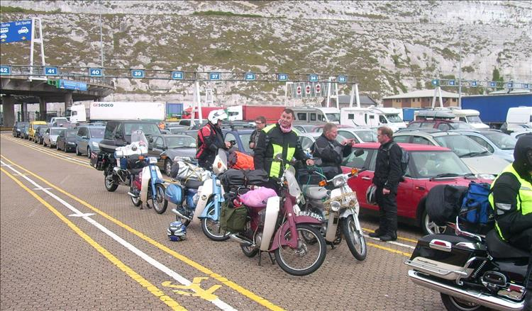 In the queue of cars and trucks is a group of riders all on C90s ready to tour in Europe