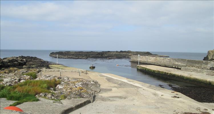 A wall and a slipway and some rocky outcrops form the small harbour at Dunseverick