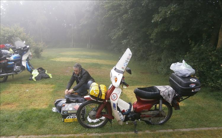 A rider is packing his camping gear onto a Honda C90 in the misty murky fog of the campsite