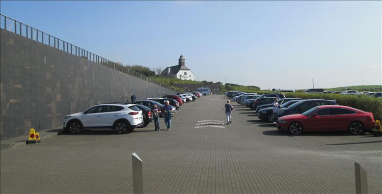 A large car park and stout almost fortress like modern wall at the Giant's Causeway
