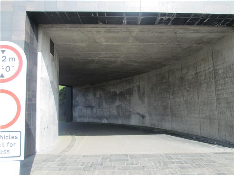 A large concrete and modern tiled entrance tunnel, imposing, unwelcoming