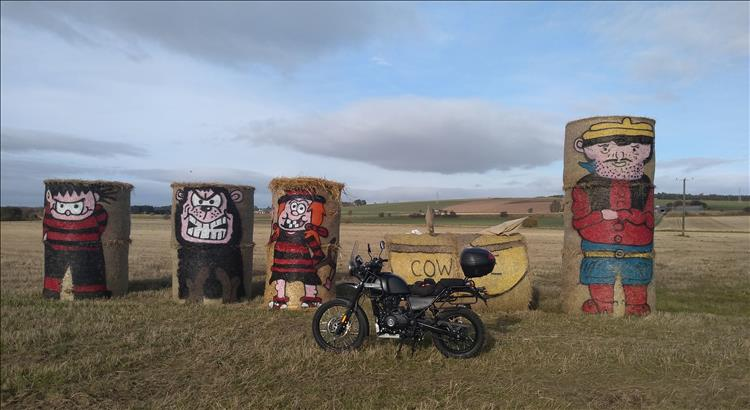 The Royal Enfield Himalayan in a field with large straw bales painted to look like Beano Characters