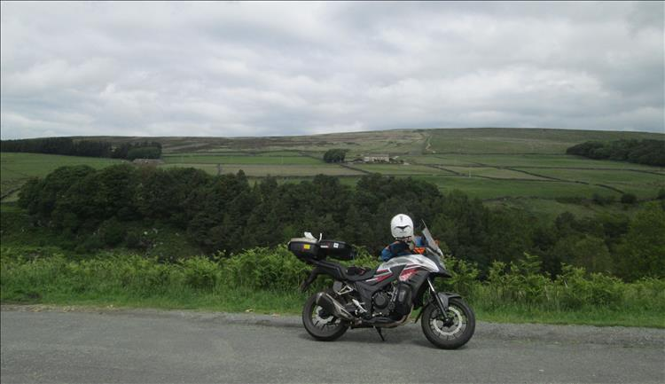 Rens motorcycle set against the farmland and trees and hills