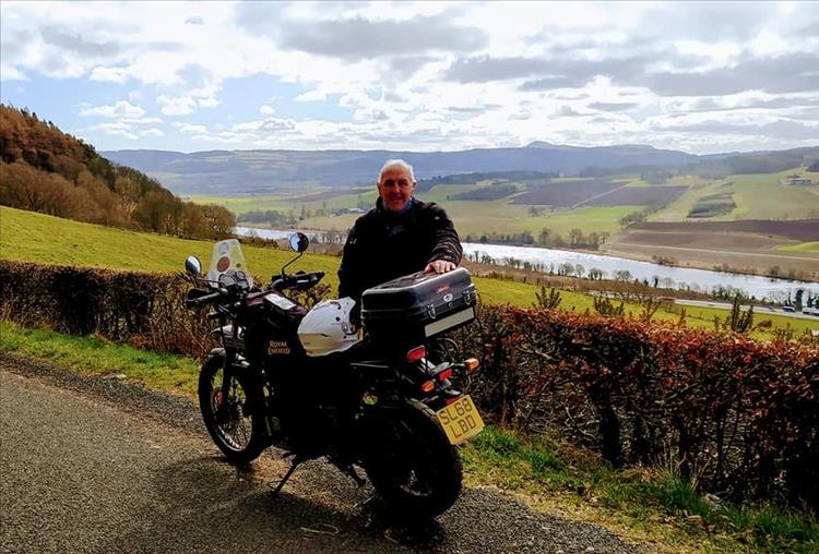 Steve stands by his Enfield against a beautiful rolling hills backdrop