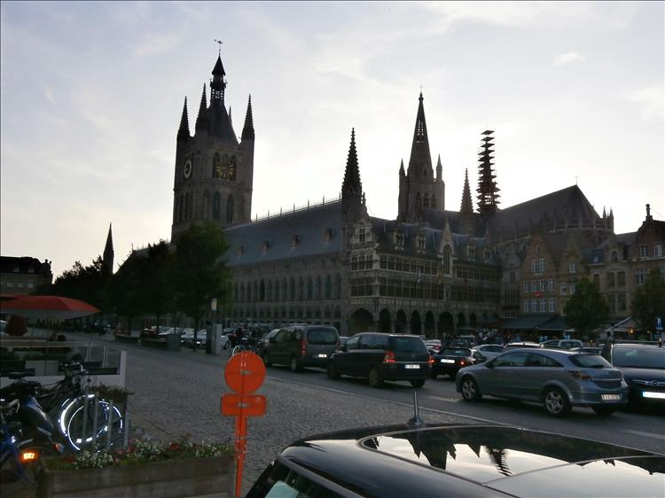 A large ornate church and cars parked in the town square at Ypres