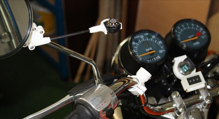 The setup, the compass is stuck out from the mirror stem and the compensating magnet is mounted on the bars