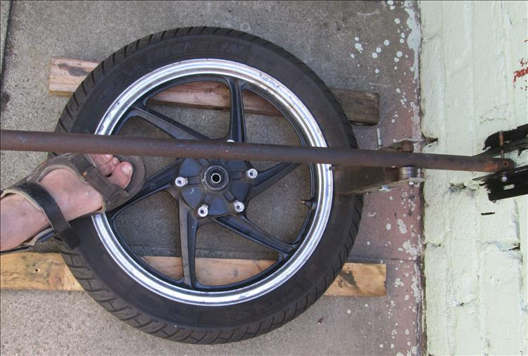 The wheel is supported on 2 lengths of wood to keep it off the floor and prevent scratching