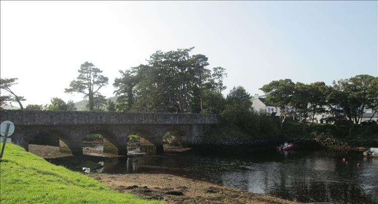 An old stone bridge with several arched spans crosses the gentle river at Cushenden