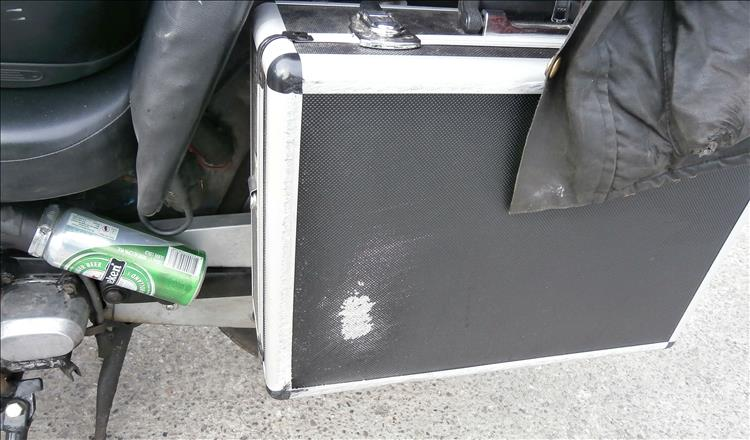 A travel case being used as a pannier has a patch of scratching after the crash