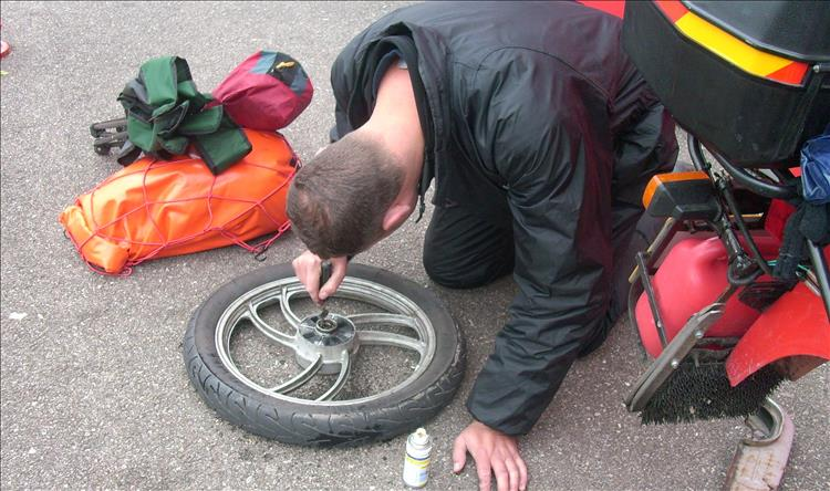 on the tarmac of a car park a rider pokes out swarf and grease from the collapsed wheel bearing