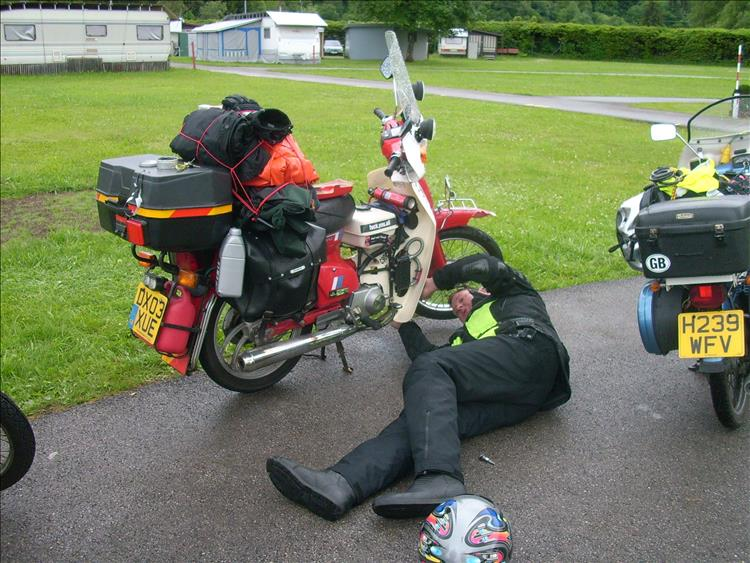 A c90 with luggage, a lot of luggage and the rider lying on the floor fixing some part of the bike