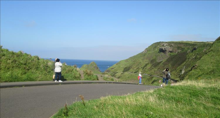 A tarmac lane leads down through green hillsides with the sea in the distance