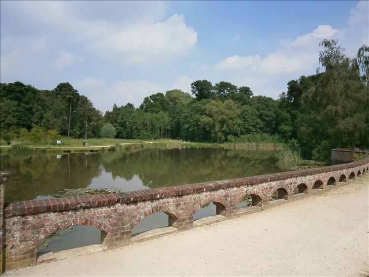 A low ornate brick wall in front of a large pond and lush green trees at the pretty park in Passchendaele