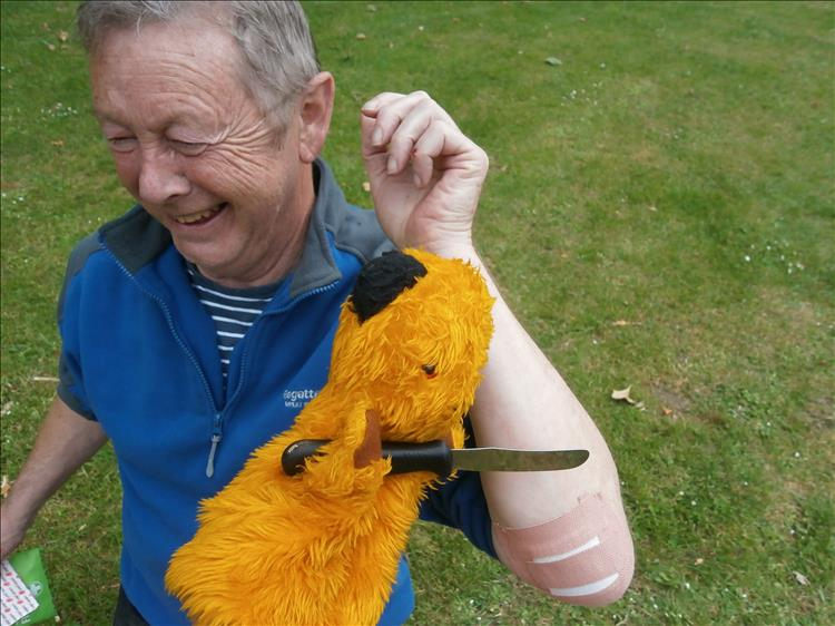 The hand puppet sooty has a knife and is pretending to do surgery on Ironsides Elbow