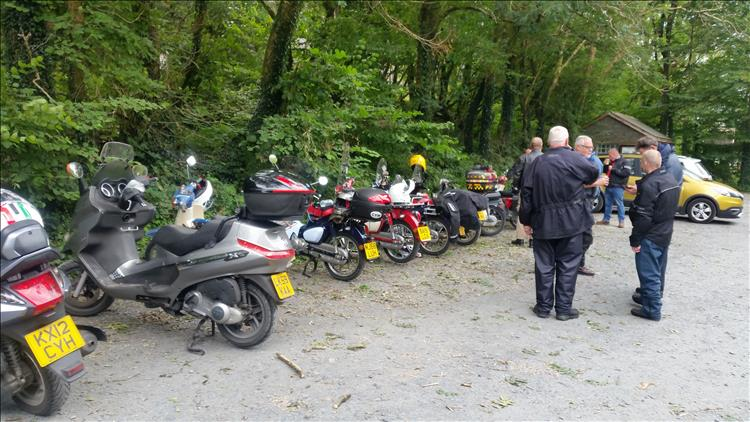 Various scooters and a variety of Honda Cubs parked up as the riders chat