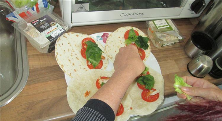 Sharon is preparing tortillas with pepperoni and salad and coleslaw