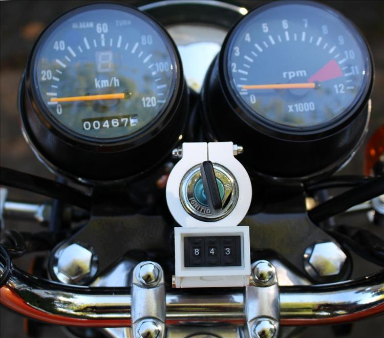 The meter in a 3D printed plastic housing, attached to the key barrel of the motorcycle