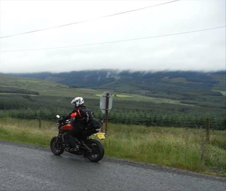 A rider on his motorcycle under heavy skies getting very wet