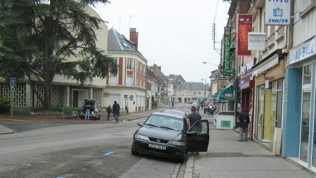 a french street with shops and wide road