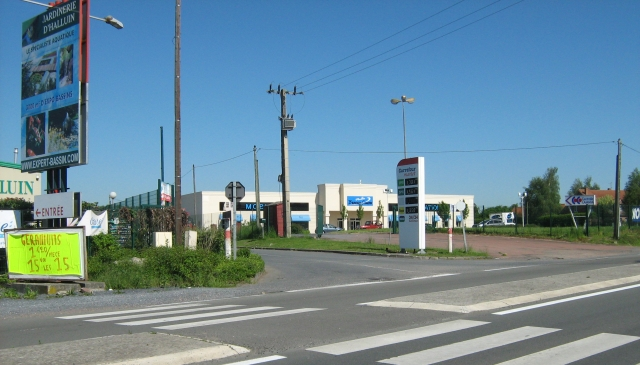 a french street with supermarket, crossing and billboards