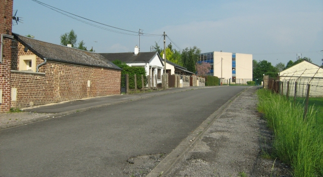 a plain street in france with a big square building at the end