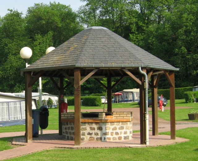 an octagonal wood and slate shelter with brick built barbeques underneath