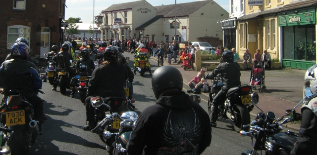 A group of bikers on their motorcycles in a parade through the town's streets