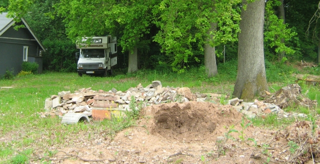 building rubble and an old tree stump with grass and a campervan in the distance